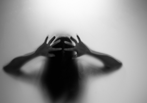 Silhouette of a woman behind the glass.