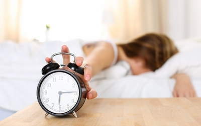 Sleepy young woman trying kill alarm clock while bury face in pillow. Early wake up, not getting enough sleep, getting work concept. Female stretching hand to ringing alarm willing turn it off