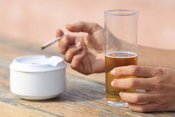 Woman hands holding a cigarette smoking and drinking alcohol in a bar table